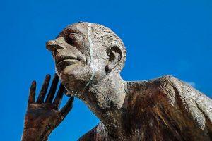 Une statue d'un homme, la main à l'oreille, qui cherche à bien entendre