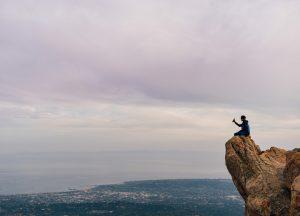 Un homme, sdu haut d'une falaise, s'apprête à jeter une bouteille à la mer